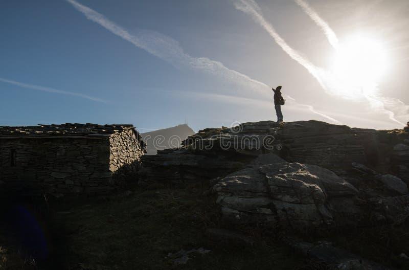 站立在与太阳后面光和山la rhune的小山顶部的愉快的人剪影在后面,巴斯克国家,法国 免版税库存照片