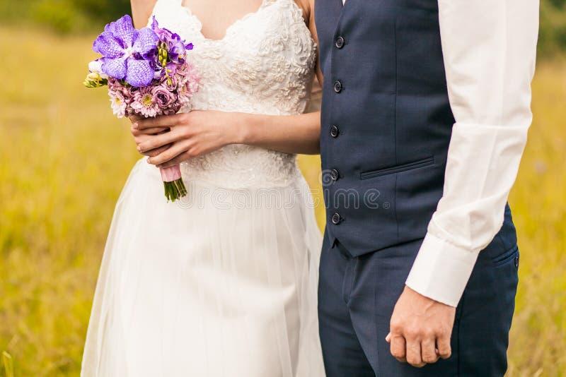 站立在与婚礼花束的仪式的新娘和新郎 免版税库存照片