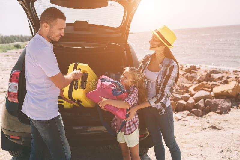 站立在与手提箱和袋子的被打开的汽车起动附近的年轻夫妇 爸爸、妈妈和女儿由海旅行 免版税图库摄影