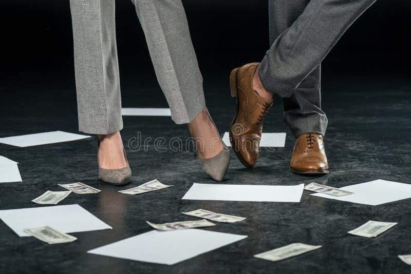 站立在与文件和美元钞票的地板上的播种的观点的买卖人, 免版税库存照片