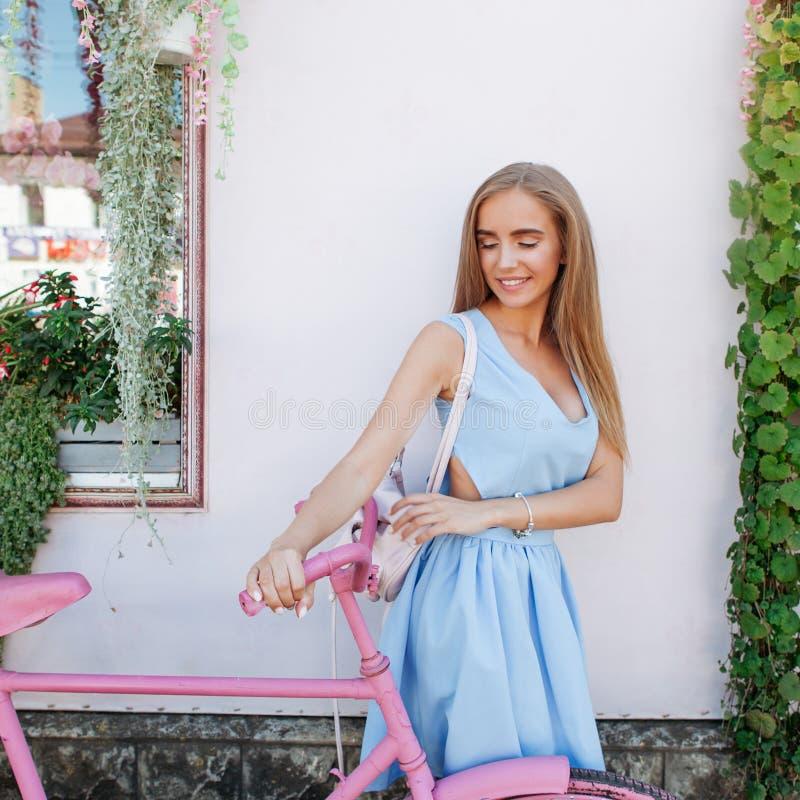 站立在与桃红色自行车的背景的被启发的匀称妇女在蓝色礼服 概念生活方式 免版税库存照片