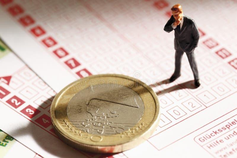 站立在与欧洲硬币的打赌事故,关闭的经理小雕象 免版税库存图片