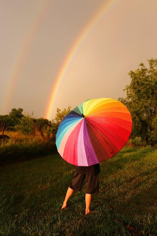 站立在与看双的五颜六色的伞的雨中的孩子 免版税库存图片