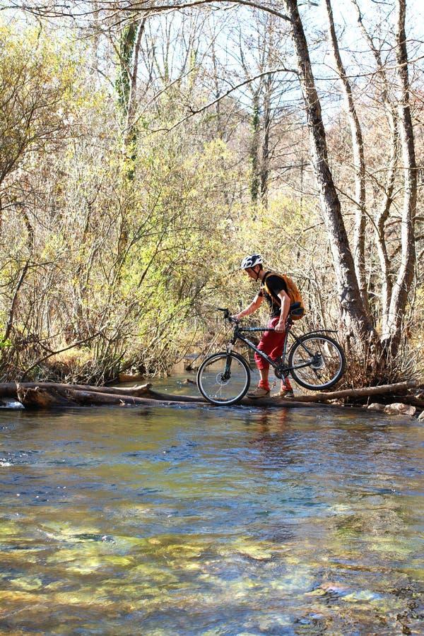 站立在与自行车的一个岩石的年轻运动员 免版税库存照片