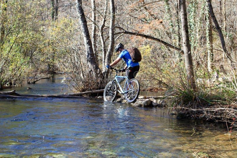 站立在与自行车的一个岩石的年轻运动员 库存图片