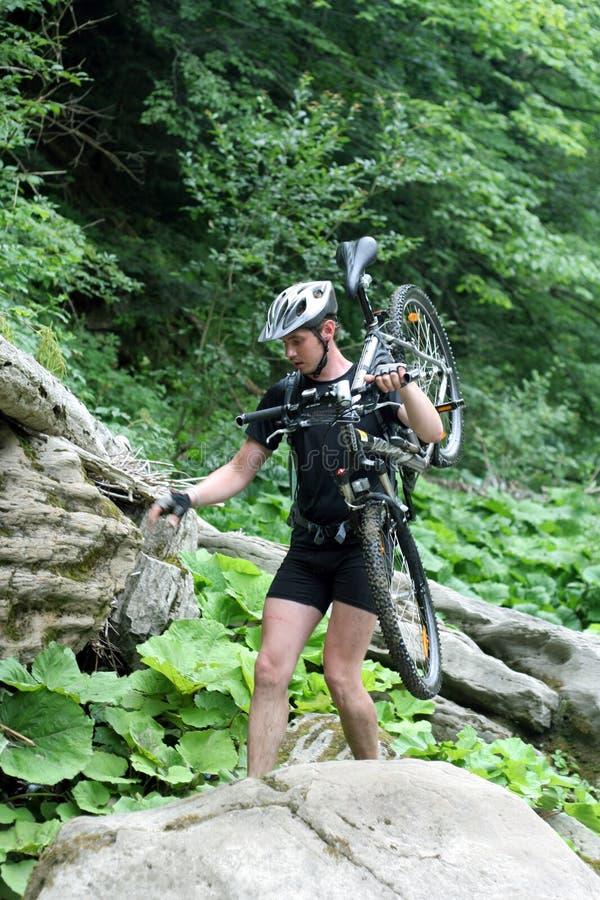 站立在与自行车的一个岩石的年轻运动员 库存照片