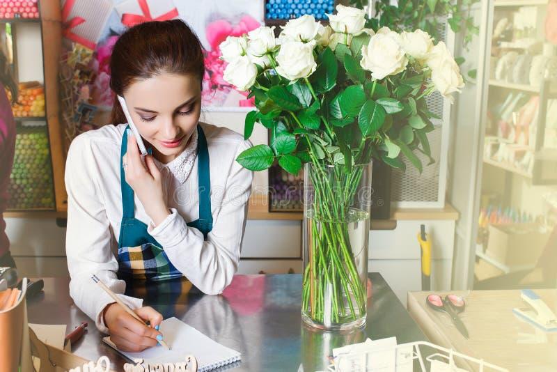 站立在与花的桌附近的微笑的卖花人画象 库存图片