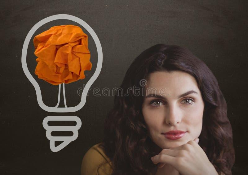 站立在与被弄皱的纸球的电灯泡旁边的妇女在黑板前面 皇族释放例证