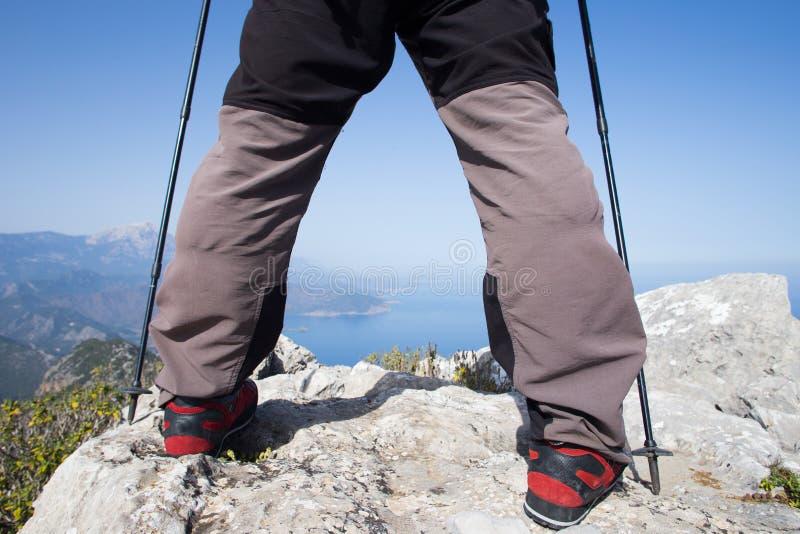 站立在与谷的山顶部的远足者在背景 图库摄影