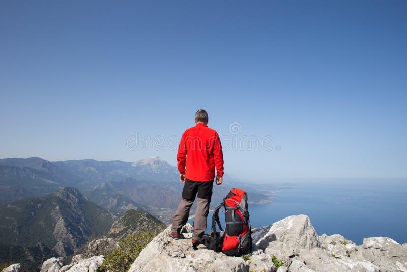 站立在与谷的山顶部的远足者在背景 库存照片