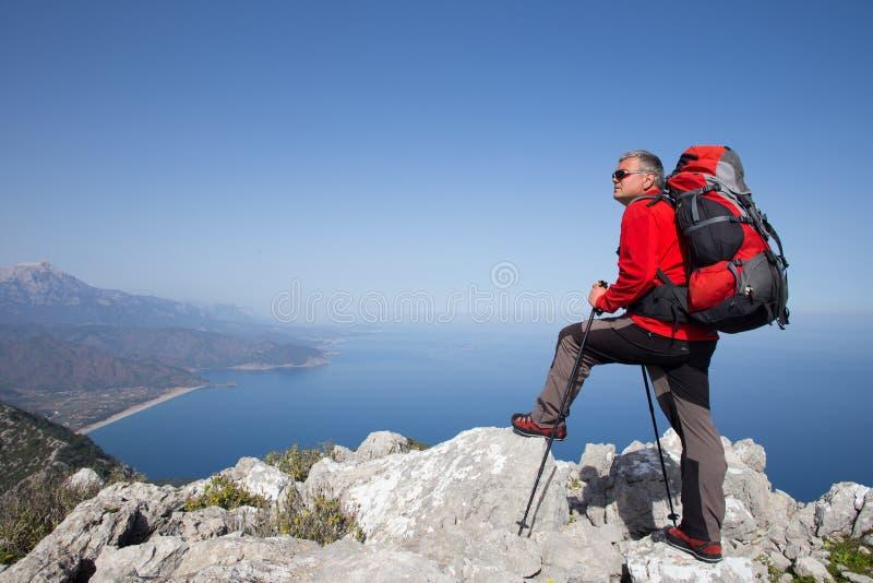 站立在与谷的山顶部的远足者在背景 免版税图库摄影