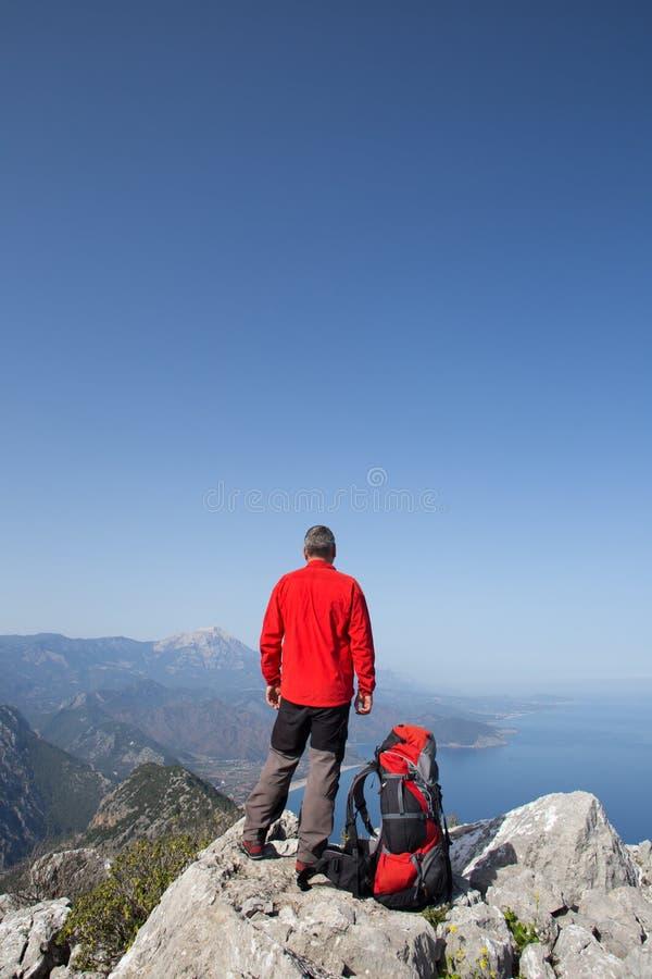 站立在与谷的山顶部的远足者在背景 免版税库存图片