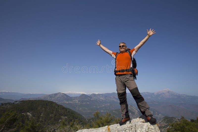 站立在与谷的山顶部的远足者在背景 库存图片