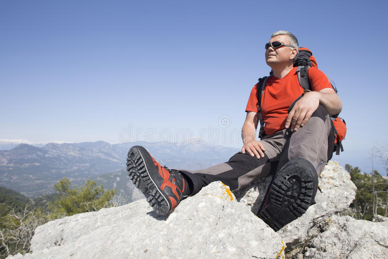 站立在与谷的山顶部的远足者在背景 免版税库存照片