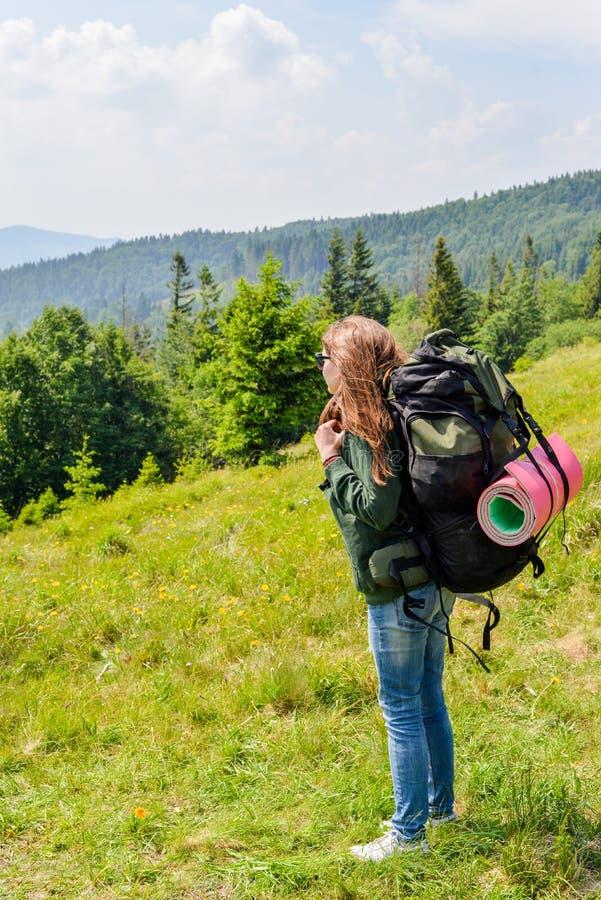 站立在与谷的山顶部的年轻步行的妇女在背景 免版税库存照片