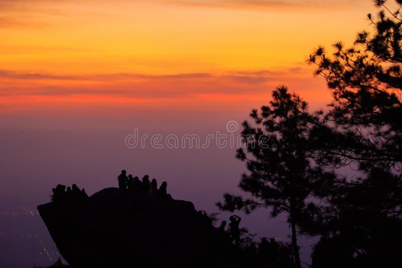 站立在与轻的日出的岩石的旅客剪影 免版税库存照片