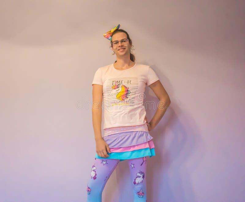 站立在与逗人喜爱的娘儿们独角兽成套装备的女性姿势的LGBT性别奇怪人 库存照片