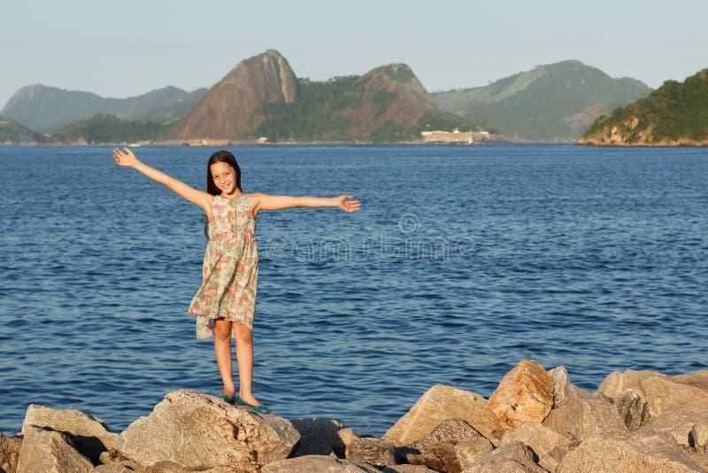 站立在与长的b的石头的愉快的微笑的美丽的青少年的女孩 库存图片