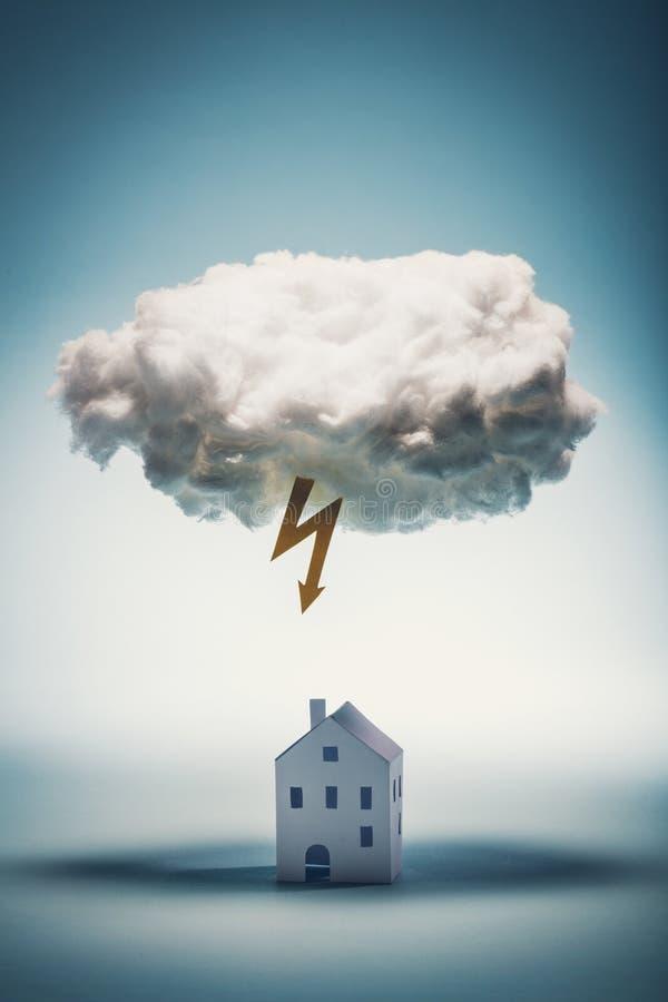 站立在与黄色闪电的一朵白色云彩下的纸房子 免版税库存图片