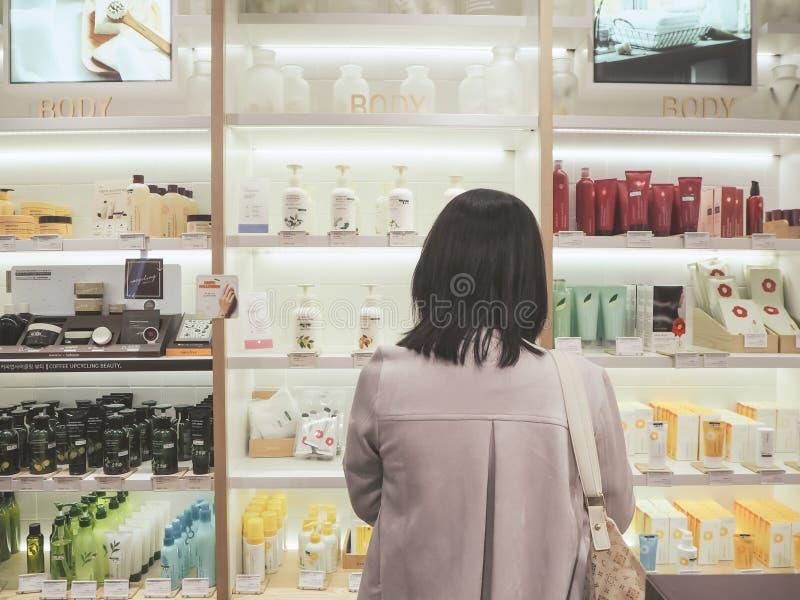 站立在与skincare产品的一个架子前面的年轻亚裔妇女 免版税图库摄影
