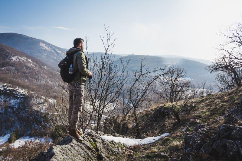 站立在举行a的冬天山的峭壁顶部的年轻人 免版税图库摄影