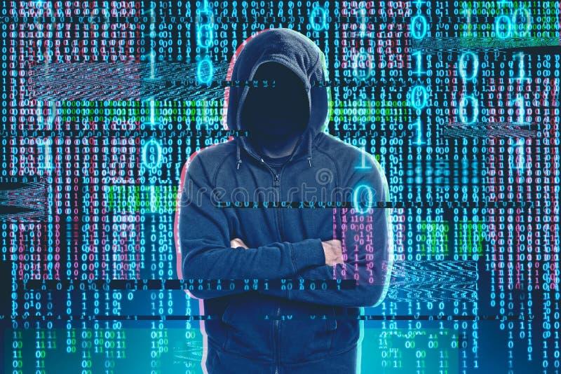 站立在二进制数雨的匿名黑客 免版税库存照片