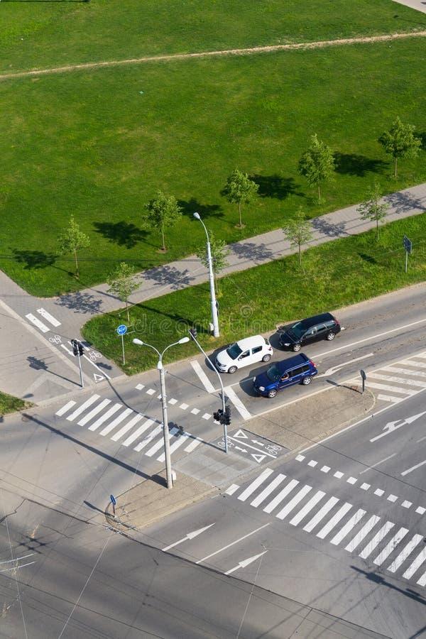 站立在交叉路的,鸟瞰图行人穿越道前面的汽车 库存图片