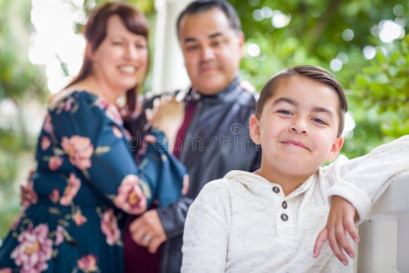 站立在他们的年轻儿子后的混合的族种夫妇 免版税库存照片