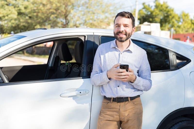 站立在他的汽车旁边的愉快的中间成人人 免版税库存照片