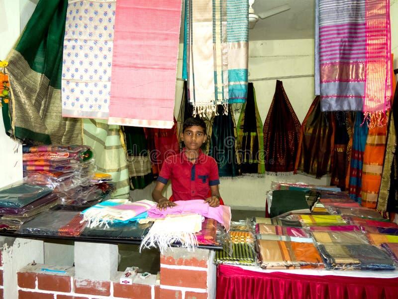 站立在他的精品店织品/服装店的年轻男孩所有者 图库摄影