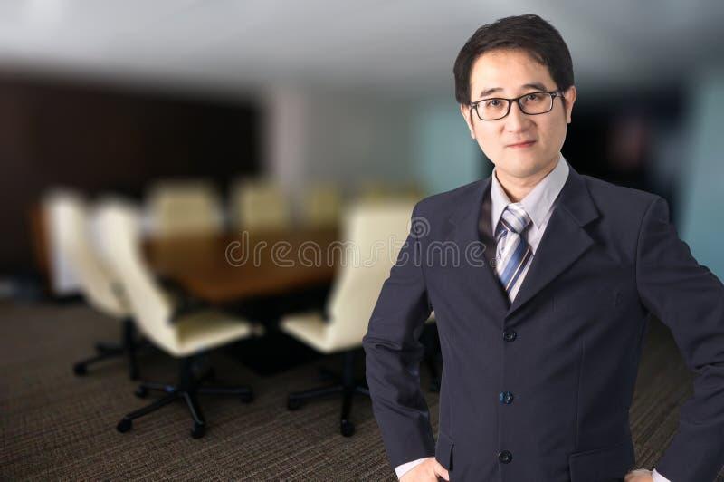 站立在会议室前面的确信的亚洲商人 免版税库存图片