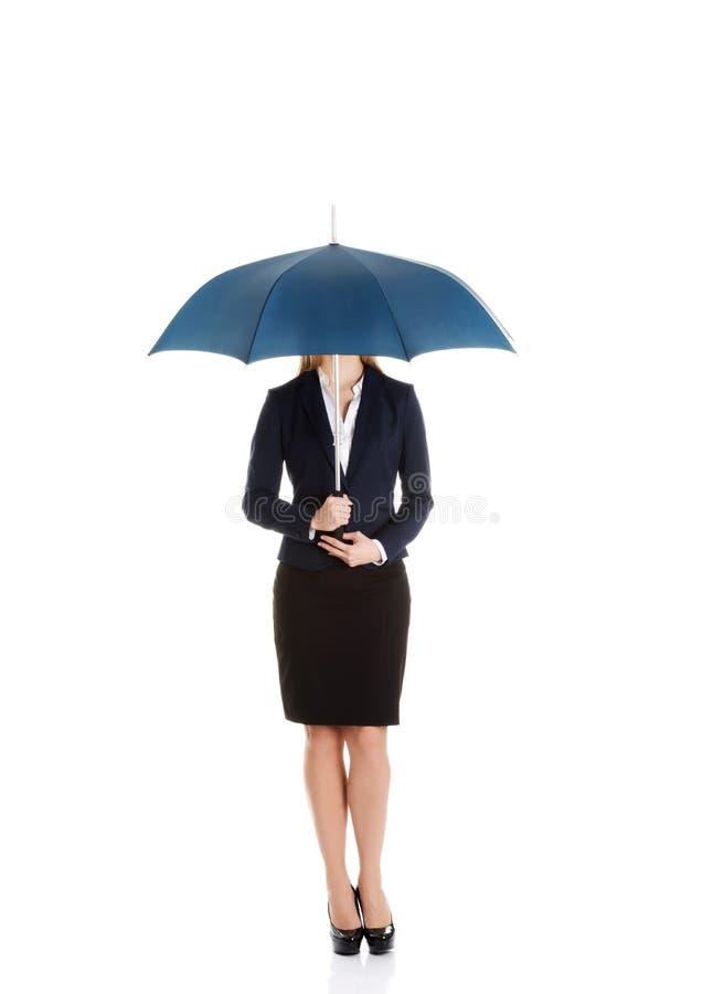 站立在伞下的美丽的白种人女商人。 免版税库存照片