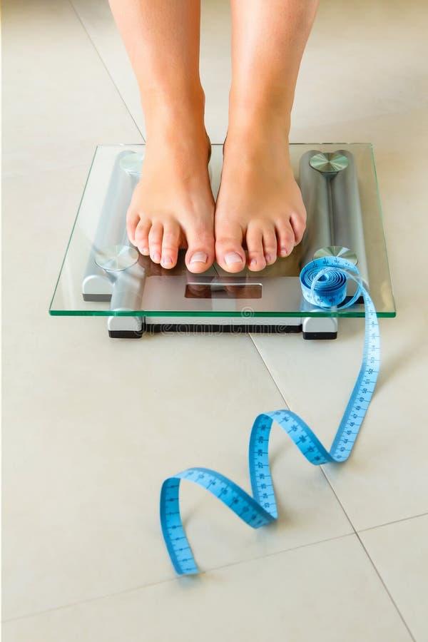 站立在体重计和磁带的妇女脚 免版税库存图片