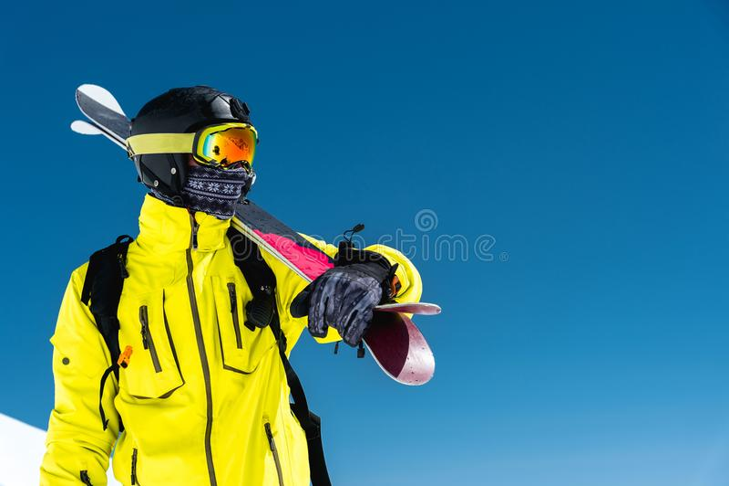 站立在倾斜的滑雪者 一套轻的衣服、盔甲和面具的人在滑雪将滑雪 在积雪覆盖的背景中 图库摄影