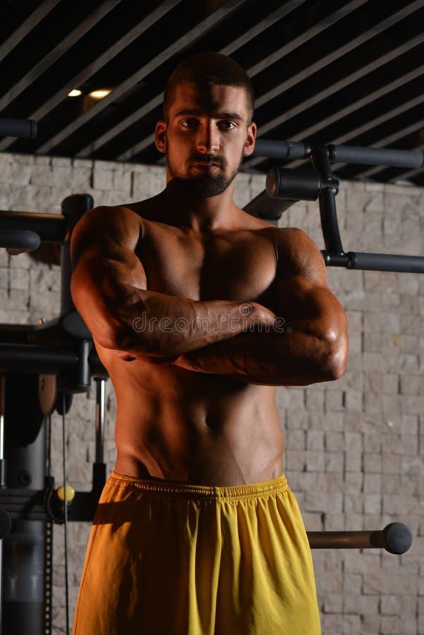 站立在健身房的严肃的年轻爱好健美者 库存照片