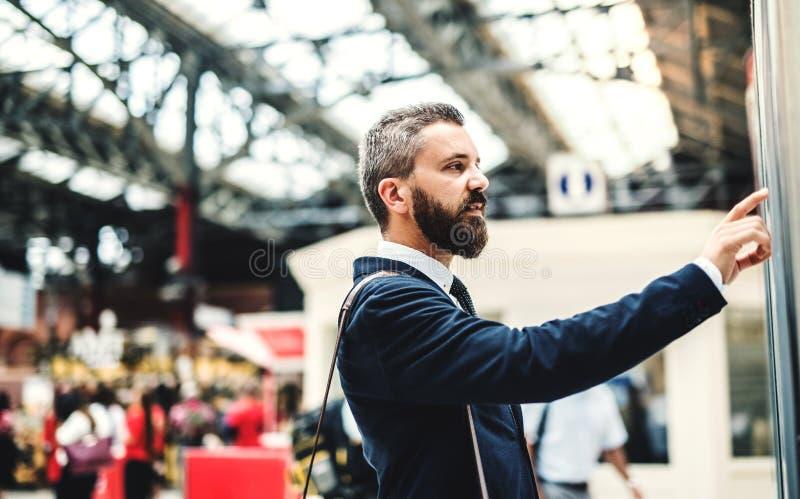站立在公共汽车或火车站的行家商人,检查时间表 库存照片