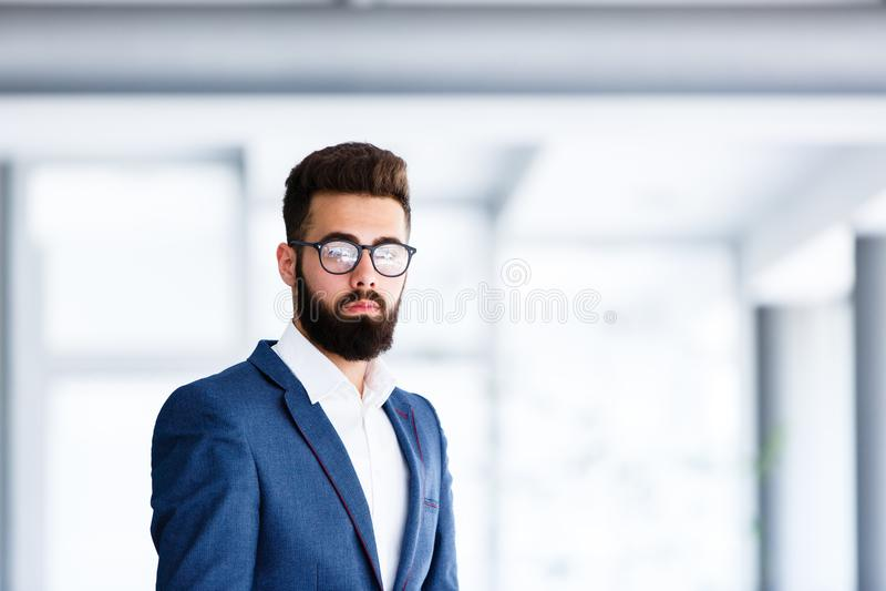 站立在公司` s的年轻英俊的商人室内 免版税库存图片