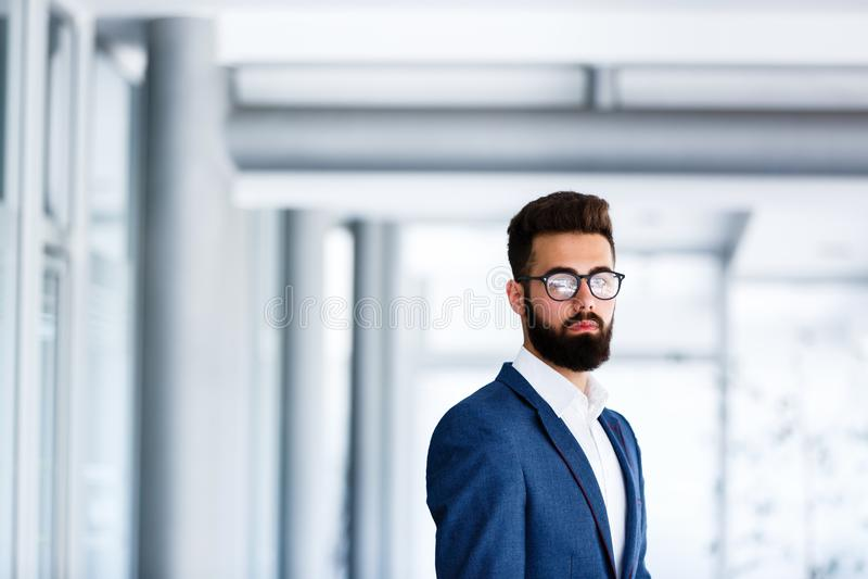 站立在公司` s的年轻英俊的商人室内 图库摄影