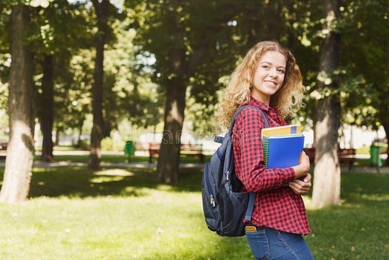站立在公园的愉快的女学生 免版税库存图片