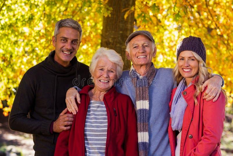 站立在公园的愉快的家庭画象 库存照片