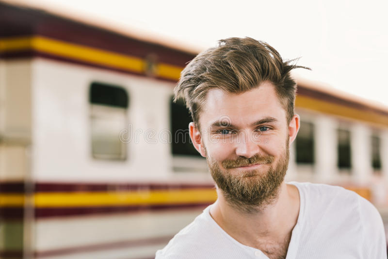 站立在公开火车站的微笑的英俊的欧洲人画象  愉快的背包旅客或假日假期旅游业 库存图片