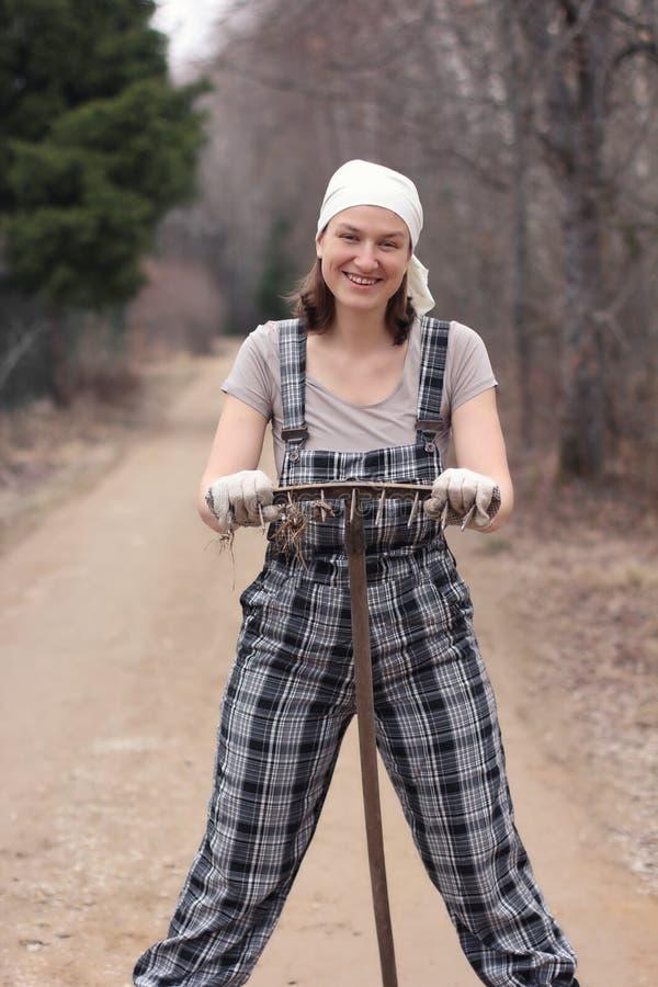 站立在农村路的花匠或农夫妇女,倾斜在 免版税库存照片