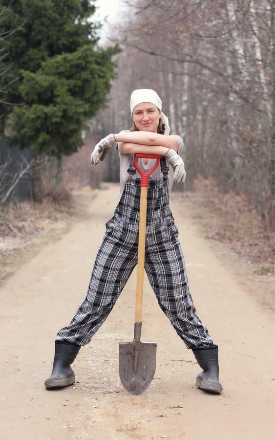站立在农村路的花匠或农夫妇女,倾斜在 免版税图库摄影