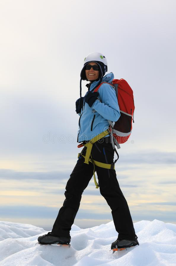 站立在冰川冰冷的上面的妇女登山人  免版税图库摄影