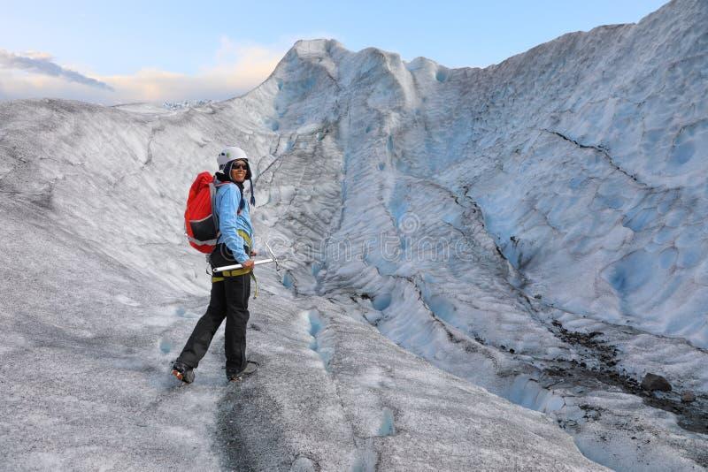 站立在冰川的裂缝的妇女登山人 免版税库存照片