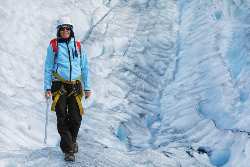 站立在冰川的裂缝的少妇登山人 免版税库存图片