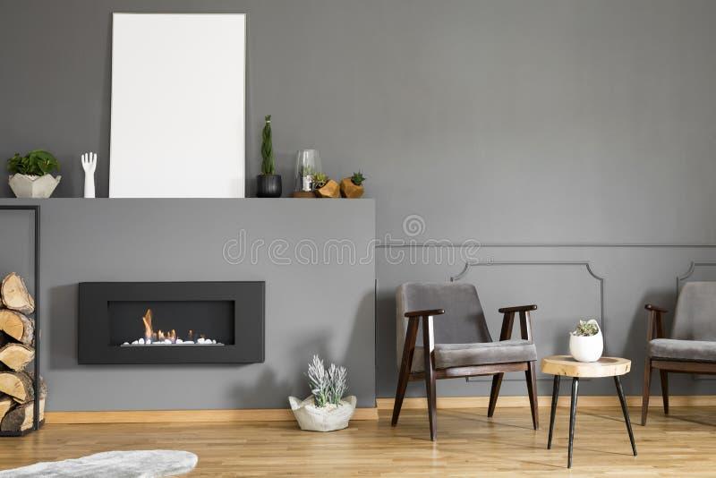 站立在凳子和firep旁边的两把扶手椅子真正的照片  免版税库存照片