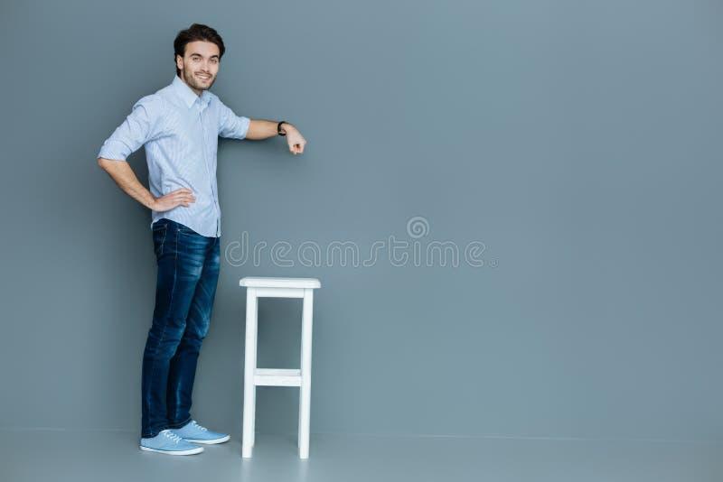 站立在凳子附近的好英俊的人 免版税库存照片