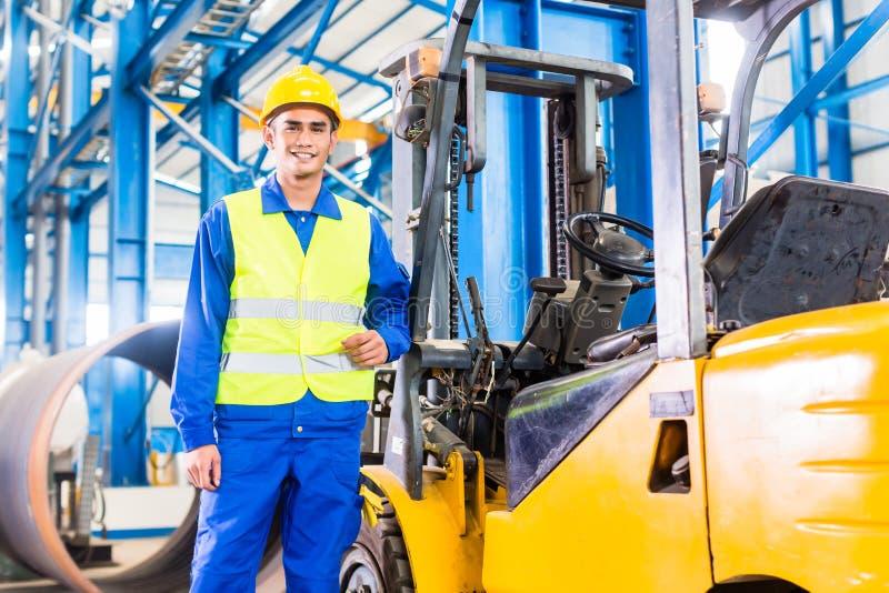 站立在制造工厂的铲车司机 免版税库存照片