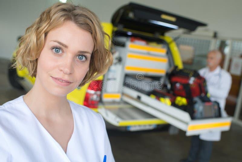 站立在前面救护车的画象女性医生 免版税库存照片